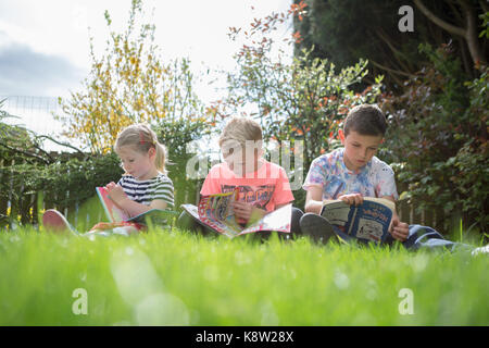 children reading in the garden - Stock Photo