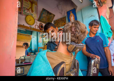 Jaipur, India - September 20, 2017: Barber shaving a man using an open razor blade on the ghats in Jaipur - Stock Photo