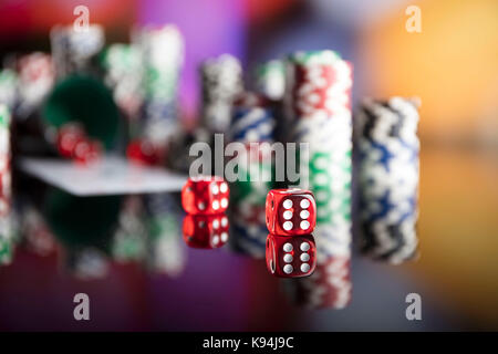 Casino theme. High contrast image of casino roulette, poker game, dice game, poker chips on a gaming table, all - Stock Photo