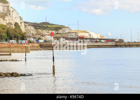 Ferry Port of Dover with lorries entering and leaving the port, the white cliffs of Dover in the background. Dover - Stock Photo