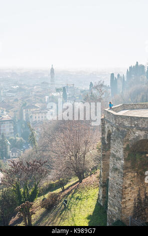 Woman standing at Venetian wall edge and watching the view of ancient italian town Bergamo. - Stock Photo