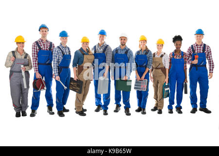 Full length portrait of confident carpenters carrying toolboxes against white background - Stock Photo