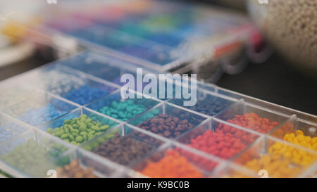 Colorful plastic granules on extruder for making plastics on extrusion manufactory - Stock Photo
