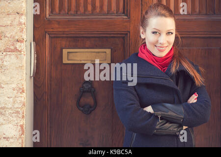Portrait of attractive young woman in front of old wooden door - Stock Photo
