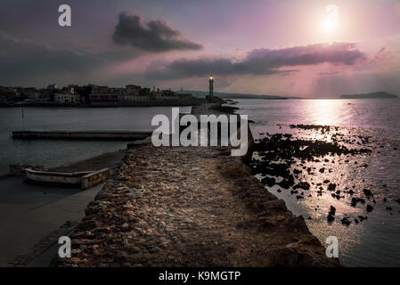 Sunset over the lighthouse and old Venetian harbor in Chania, Crete - Stock Photo