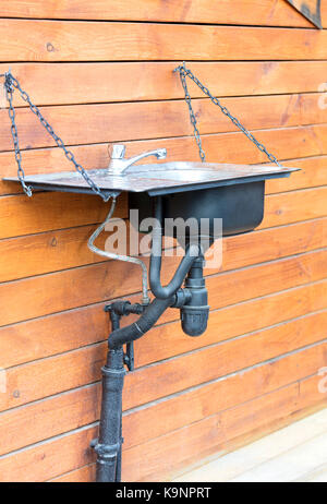 A modern washbasin sink with a stainless steel faucet installed outside on a chain on the wall of a wooden house, - Stock Photo