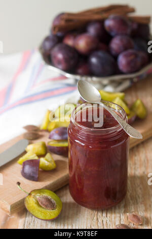 Homemade plum jam or confiture in a glass jar, and fresh plums on a wooden background. Rustic style, selective focus. - Stock Photo