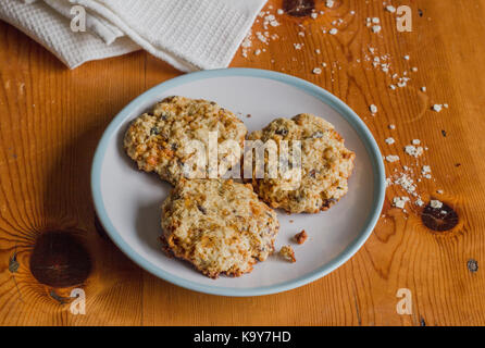 Homemade sweet and crunchy oats cookies on rustic bright wooden kitchen table with oats and white cloth - Food background - Stock Photo