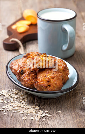 carrot and oat cookies on blue plate, a mug of milk on old wooden background - Stock Photo