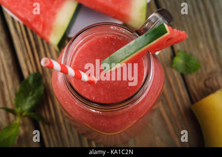 Freshly made smoothies from pieces of watermelon and a banana in a glass jar on a wooden table, top view - Stock Photo