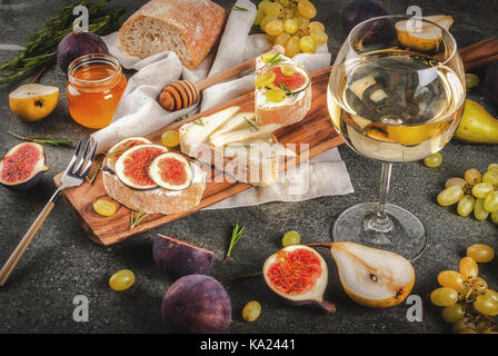 Sandwiches with ricotta or cream cheese, ciabatta, fresh figs, pears, grape, walnuts and honey on wooden board over - Stock Photo