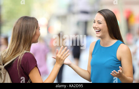Two happy friends greeting and meeting on the street - Stock Photo