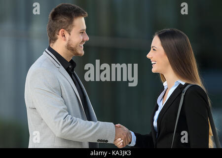 Side view of two happy executives meeting and handshaking on the street with an office building in the background - Stock Photo