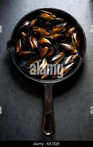 Mussels steamed on a cast-iron frying pan vertical - Stock Photo