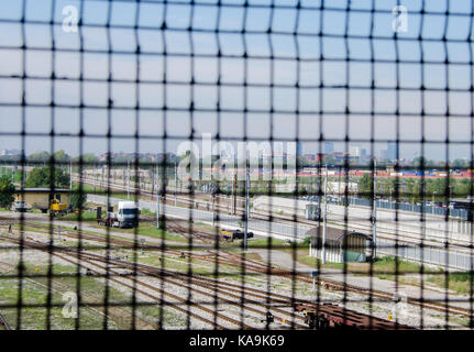Selective focus of gate with train depot and Milan, Italy downtown background - Stock Photo