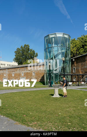 Young man taking a photograph with his cell phone in front of the Stewart Museum or Musee Stewart in Parc Jean-Drapeau - Stock Photo