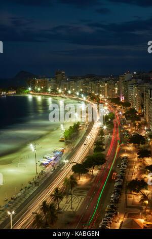 Traffic along Avenida Atlantica and Copacabana Beach at dusk, Rio de Janeiro, Brazil, South America - Stock Photo