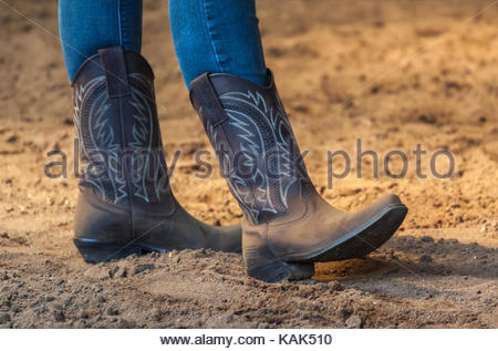 Woman in blue jeans stands relaxed on the sandy ground. Close-up of her decorated brown cowboy boots. Western riding - Stock Photo