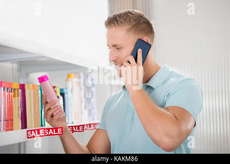 Male customer using smartphone while looking at cosmetic product in supermarket - Stock Photo