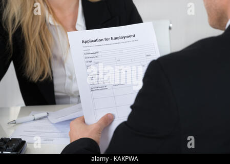 Male candidate holding application form in front of interviewer in office - Stock Photo