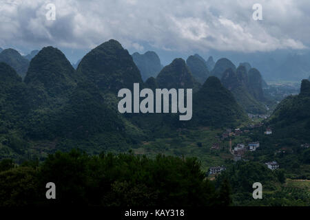 Beautiful Chinese natural landscape with karst hills, green mountains, small village, countryside near Xinping, - Stock Photo