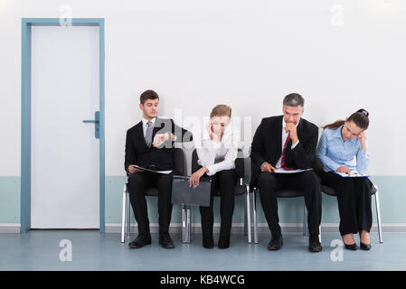 Businesspeople Sitting On Chair Waiting For Job Interview In Office - Stock Photo