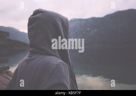 Gloomy nostalgic portrait of sad lonely melancholic adult female with hooded jacket standing on the lake shore in - Stock Photo