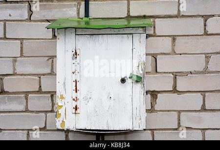 Old electric wooden box on a brick wall. - Stock Photo
