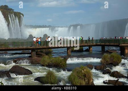 Tourists on viewing platform on Brazil side of Iguazu Falls, Brazil - Argentina border, South America - Stock Photo