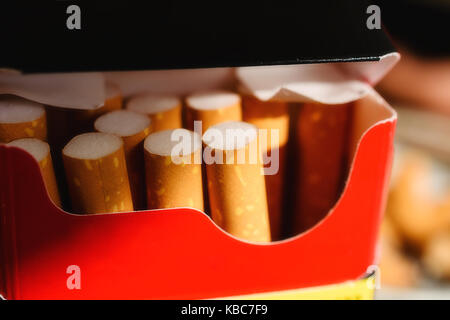 Close-Up Of Red And Black Cigarette Pack With Several Cigarettes Within - Stock Photo