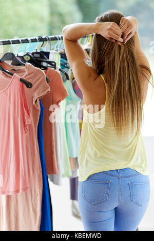 woman trying to choose between 2 dresses of different colours - Stock Photo