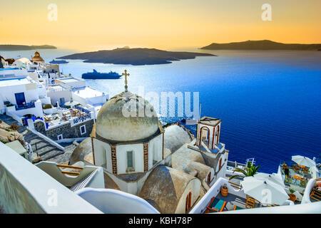 Fira, Santorini - Greek Islands landmark with white village, cobbled paths, greek orthodox blue church and sunset - Stock Photo