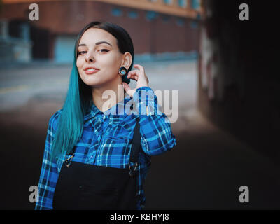 Street punk or hipster girl with blue dyed hair. Woman with piercing in nose, violet lenses, ears tunnels and unusual - Stock Photo