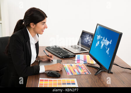 Happy Female Designer Looking At Computer While Using Graphic Tablet At Desk. Photographer owns copyright for images - Stock Photo