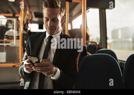 Young businessman wearing a suit smiling while standing on a bus during his morning commute reading text messages - Stock Photo