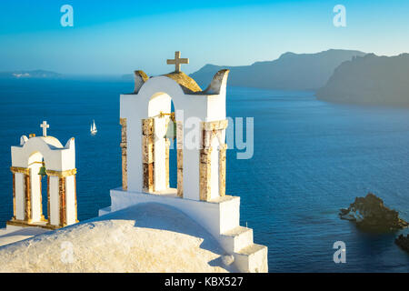 Church bells on a Greek Orthodox Church overlooking the Aegean Sea in the town of Oia on the island of Santorini - Stock Photo