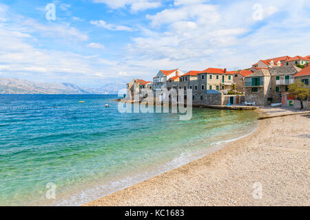 Beach in Postira town with old houses on shore, Brac island, Croatia - Stock Photo