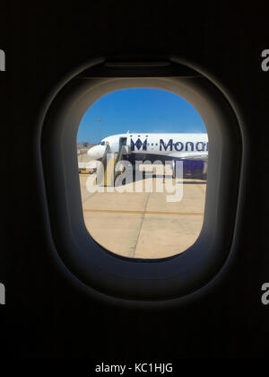A deserted Monarch plane sits on the tarmac at Faro Airport, Portugal. Seen through the window of a neighbouring - Stock Photo