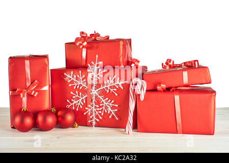 Pile of red gift boxes on white wooden table. - Stock Photo