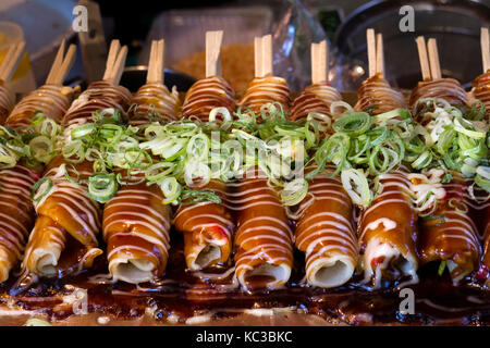 Kyoto, Japan - May 18, 2017: Baking Hashimaki,  okonomiyaki on sticks with fresh spring onions as a snack - Stock Photo