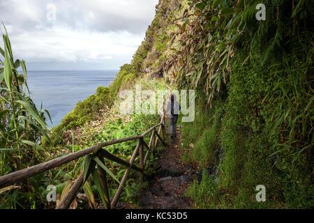 Hiker on a hiking trail on the south coast near Faja de Lopo Vaz, island of Flores, Azores, Portugal - Stock Photo