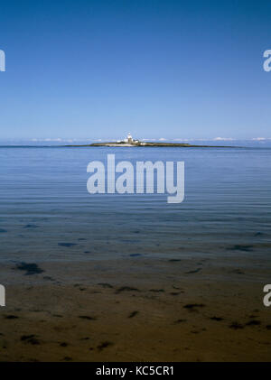 Coquet Island and lighthouse, 1.5 miles off Amble, Northumberland, at the mouth of the River Coquet, seen from beach. - Stock Photo