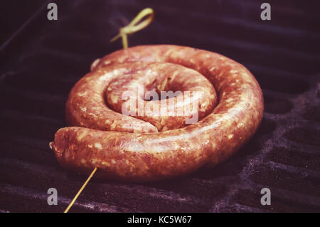 raw sausage links prior to cooking on a hot charcoal grill. fried German sausages. National cuisine. Ingredients - Stock Photo