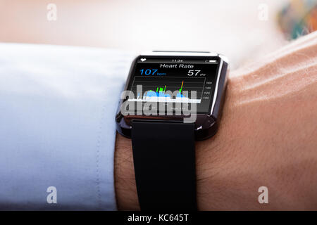 Close-up Of A Person Hand Wearing Smart Watch Showing Heartbeat Rate - Stock Photo