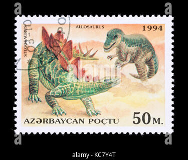 Postage stamp from Azerbaijan depicting an allosaurus and stegosaurus - Stock Photo