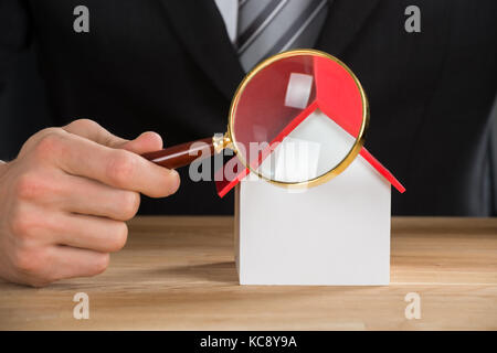 Close-up Of Businessman Holding Magnifying Glass On House Model At Wooden Desk - Stock Photo
