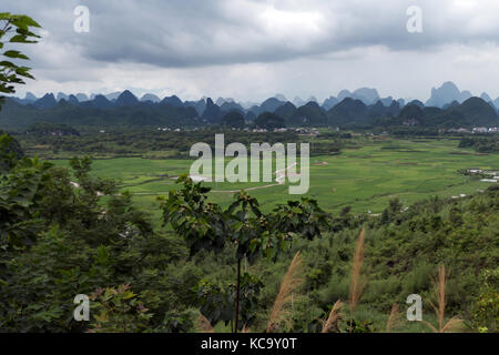 Beautiful Chinese natural landscape with karst hills, green mountains, small village, countryside between Yangshuo - Stock Photo