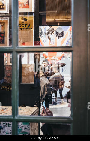 Man getting a haircut inside Hobbs Barbers, barber shop located within Borough Market, one of the largest and oldest - Stock Photo