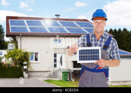 Smiling Repairman Holding Solar Panel In Front Of The House - Stock Photo