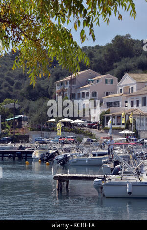 Boats, restaurants, houses and tavernas on the waterfront at the harbour in saint stefanos near kassiopi on the - Stock Photo
